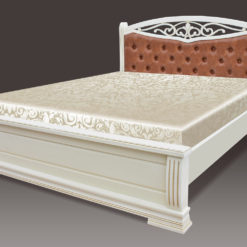 Кровать из массива дерева, изголовье которой выполнено в мягкой обивке и резным изголовьем